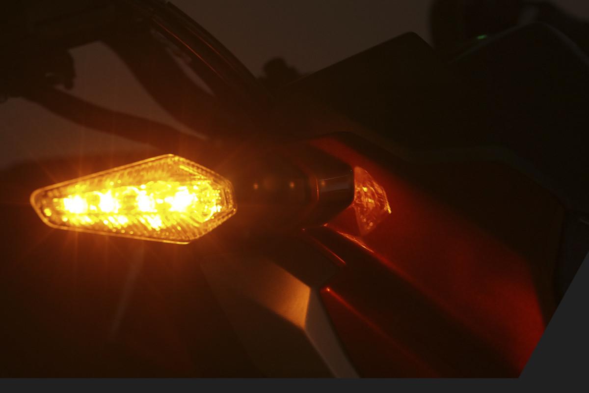 Imagem focando na seta da nova DR 160 FI, acessa, em fundo escuro