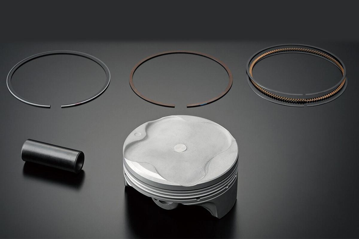 Imagem mostrando em 3D os pistões forjados em alumínio da GSX-R1000 em fundo cinza