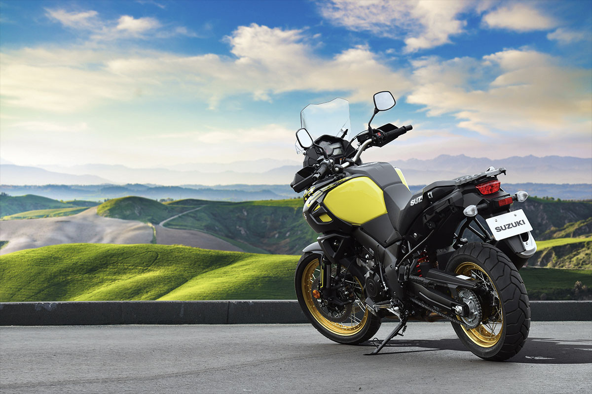 A imagem mostra a V-Strom 1000XT na cor amarela mostrando sua lateral e a parte traseira em uma paisagem com montanhas repletas de área verde.