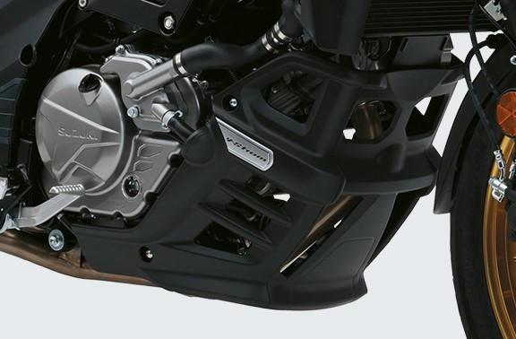 Imagem focada na proteção do motor da V Strom 650 XT em fundo cinza