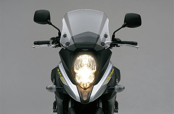 Imagem da V Strom 650 XT frontal mostrando o farol em LED em fundo cinza