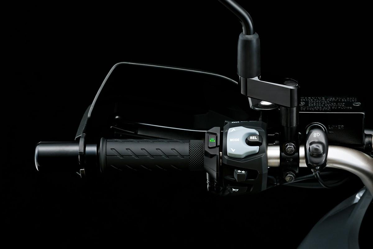 Imagem mostrando o guidão esquerdo da V-Strom 650 ADV, em fundo escuro