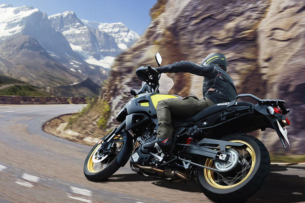 Action da V-STROM 1000AD, mostrando a traseira e lado esquerdo da moto, percorrendo curva na estrada com montanhas com neve ao fundo