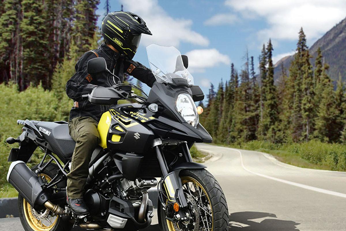 Imagem da V-STROM 1000AD estacionada na lateral da estrada, com piloto olhando para trás. A moto está sendo mostrada pela dianteira e lateral direita e ao fundo há árvores, céu azul com nuvens e nas laterais da imagem, grama