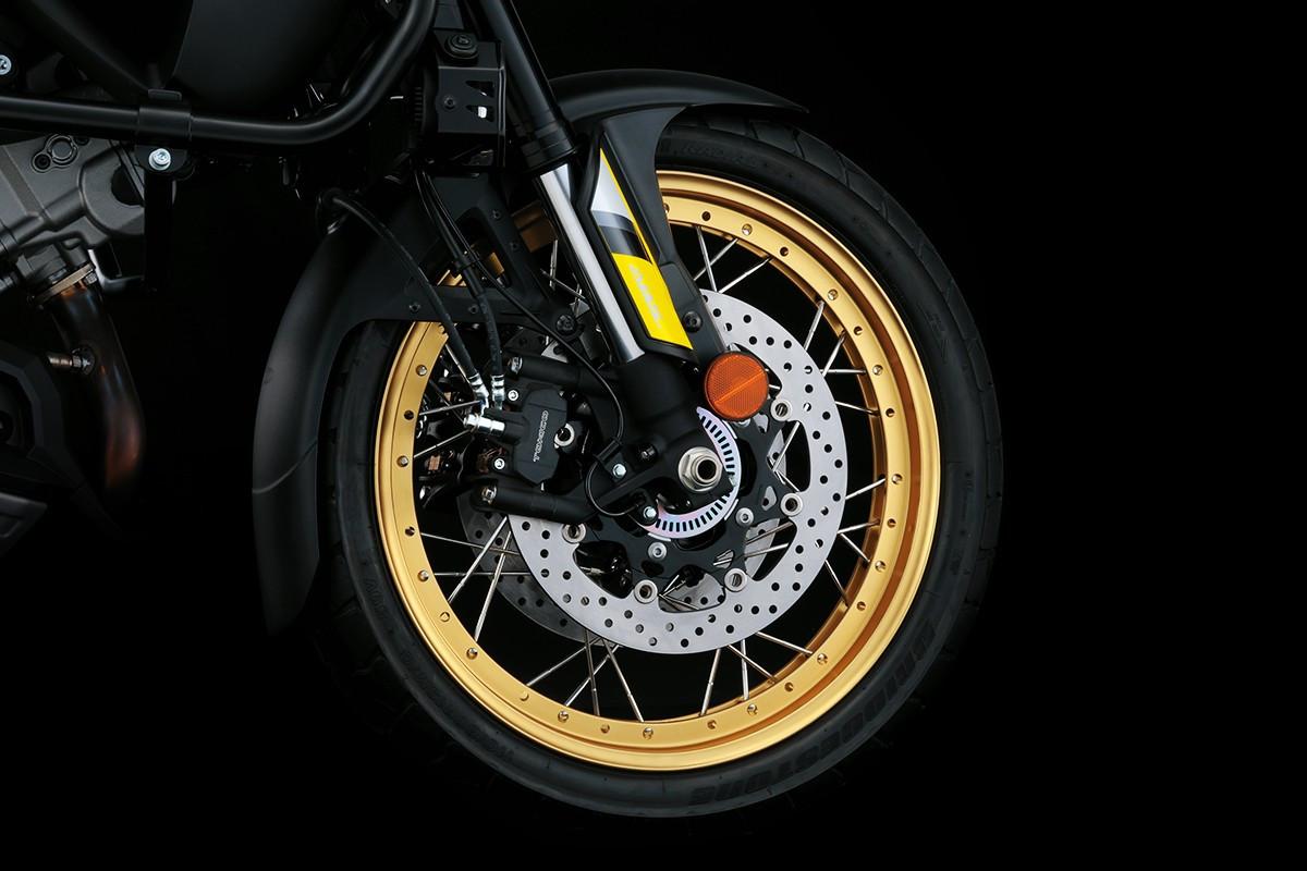 Imagem mostra roda e pinças de freio da V Strom 1000 ad em fundo escuro