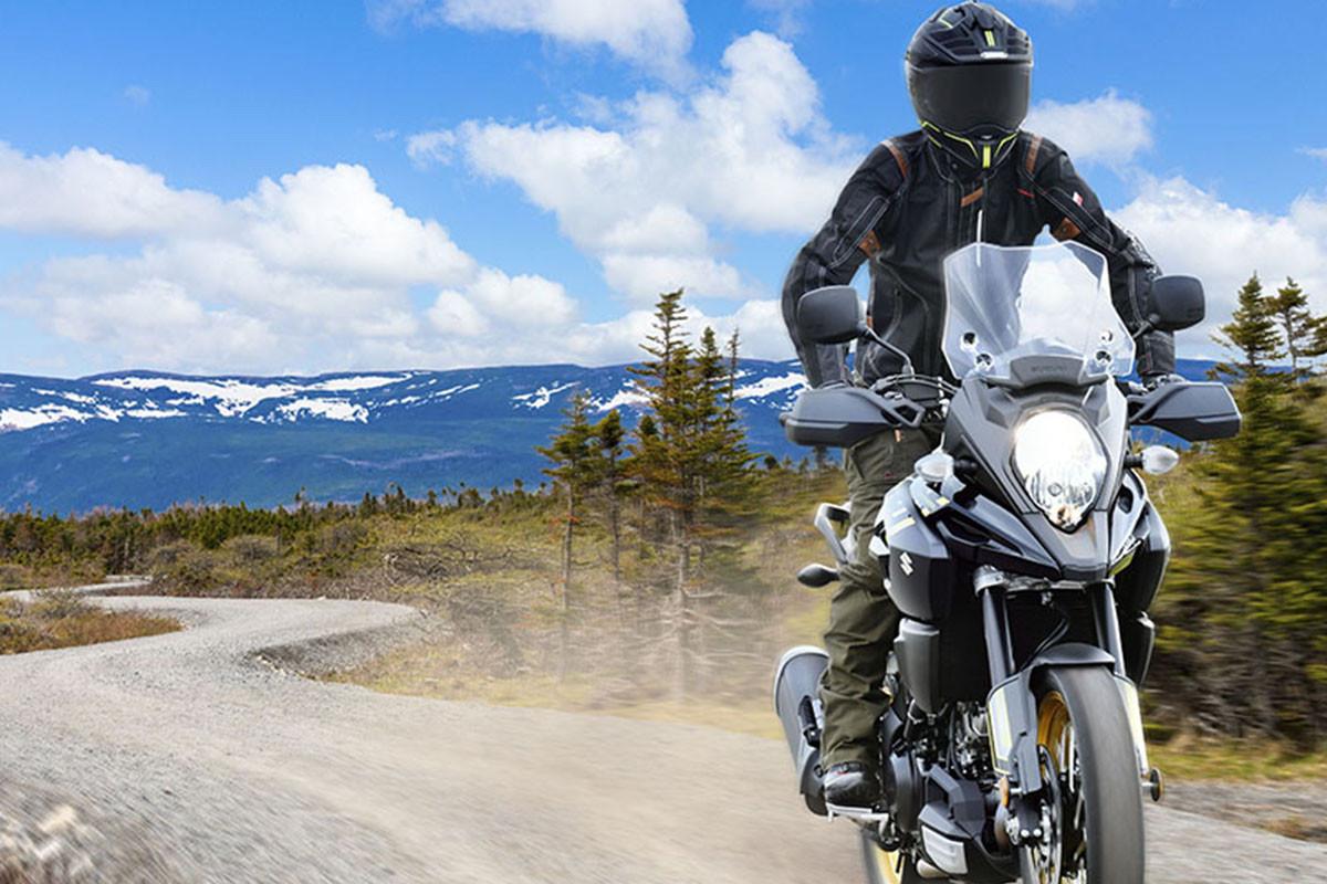 Imagem em action da V-STROM 1000AD de frente, com árvores e montanhas com neve ao fundo e céu azul com algumas nuvens